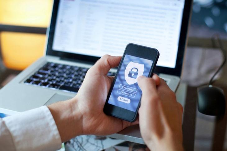 Manos de un hombre accediendo desde su smartphone a una app con sistema seguro